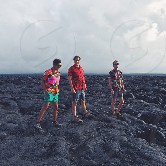 three people standing on a black rock formation photo