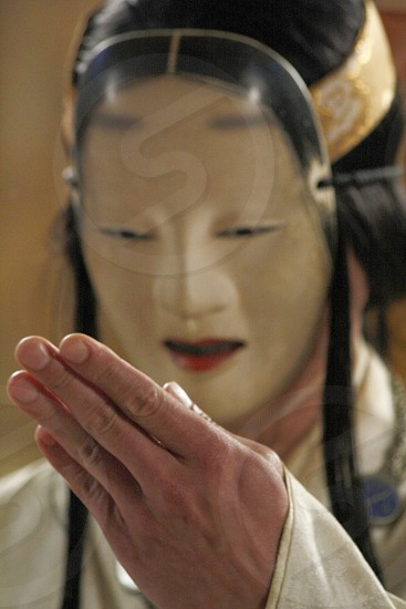 Male Noh or No theater artist wearing traditional Japanese mask performs a ritual hand gesture during a performance. photo