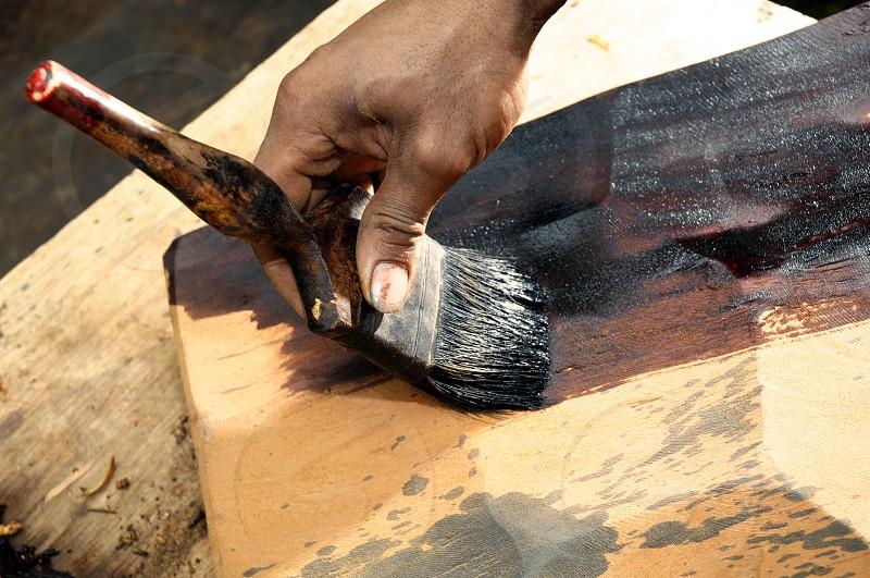 Closeup of hand painting wood. photo