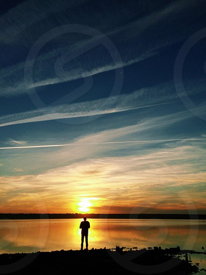 Earth sunset silhouette landscape boy men sky cloudy cloud orange red water mirror lake river sea evening light sun romantic walk nature summer spring thinking plane fly freedom free think photo