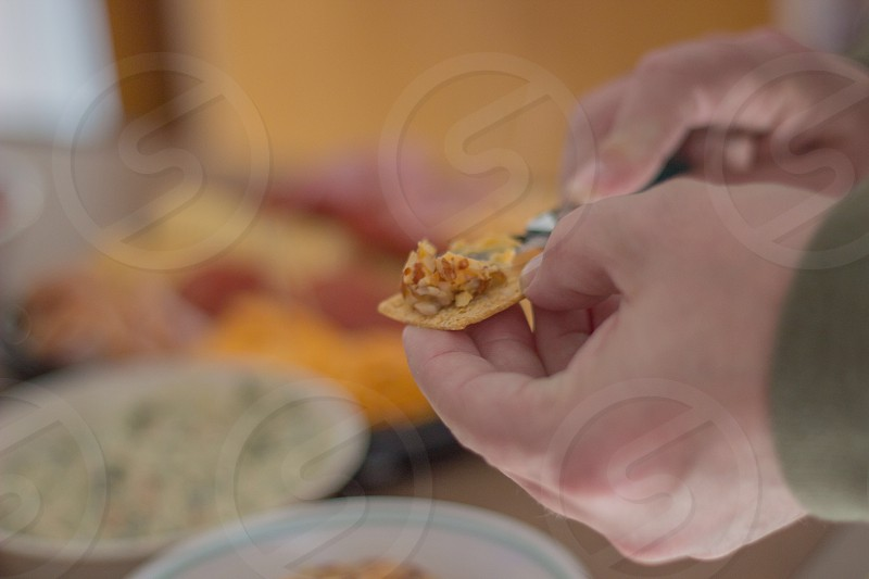 man holding cracker with toppings photo