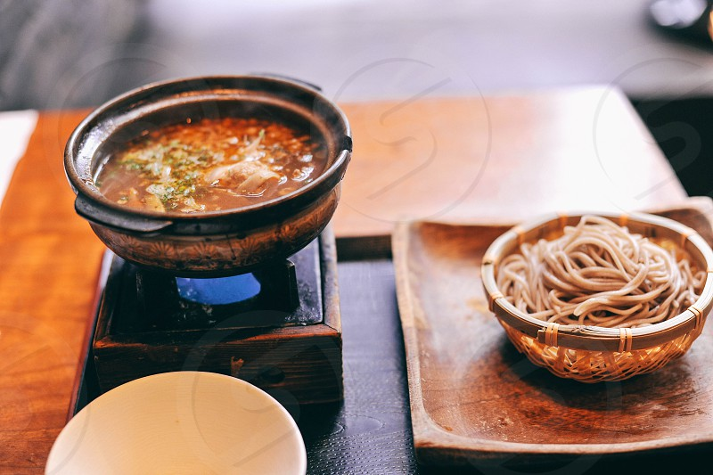 steaming soup in a bowl on a raised platform tray next to a bowl of noodles on a square wood plate on the tray photo