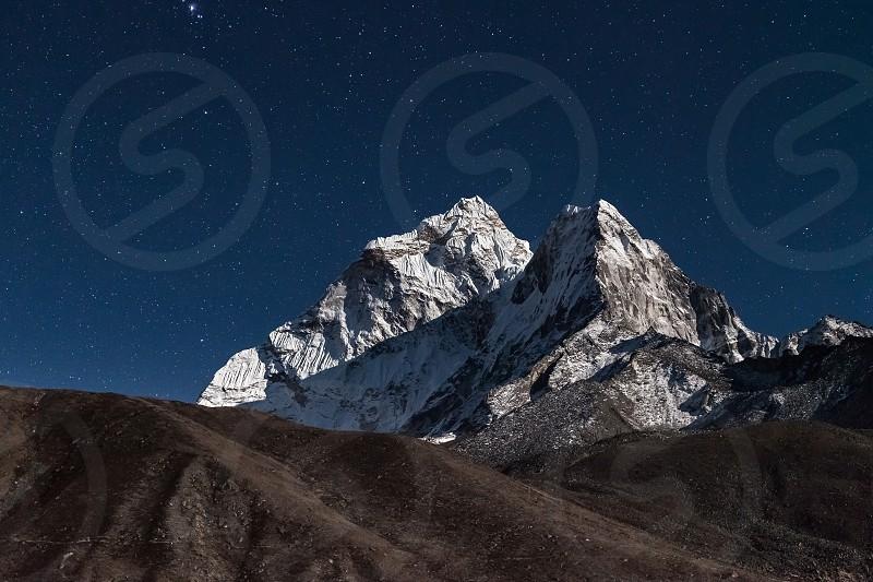 Ama Dablam mountain peak lit up by a bright moonlight on a starry night. Beautiful night mountain landscape under bright moonlight. Stars above himalayan mountain range Everest Base Camp Trek Nepal. photo