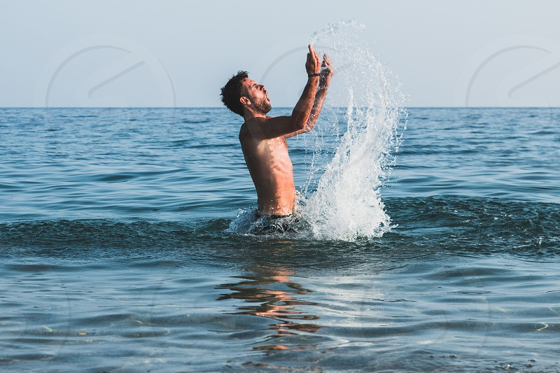 Young man splashing a water in the sea photo