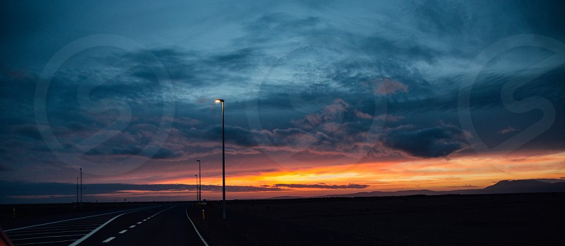 Epic sunset on the Horizon in Iceland. A road stretches off into the distance. photo