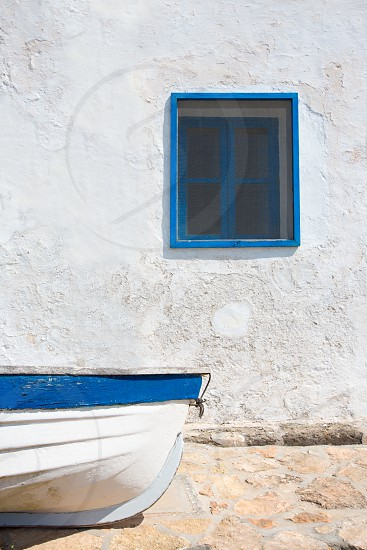 Mediterranean boat and whitewashed wall in white and blue at Balearic Islands photo
