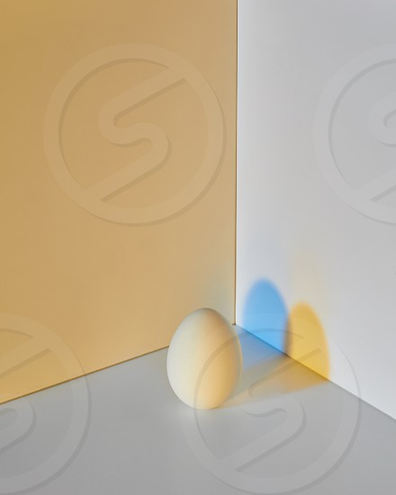 A colored gray-yellow egg with a reflection of blue-yellow shadows around a double yellow-gray background with copy space. Easter concept. photo