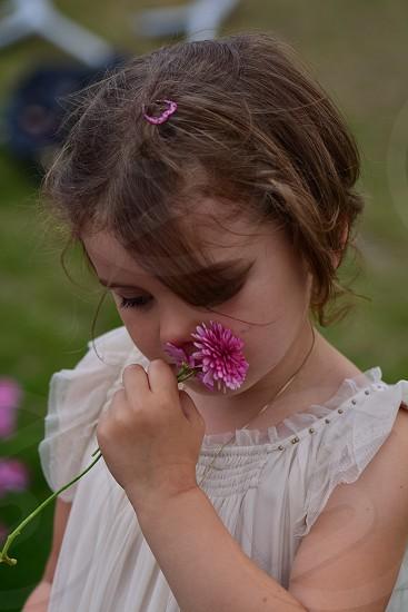girl in white ruffle shirt sniffing flower photo