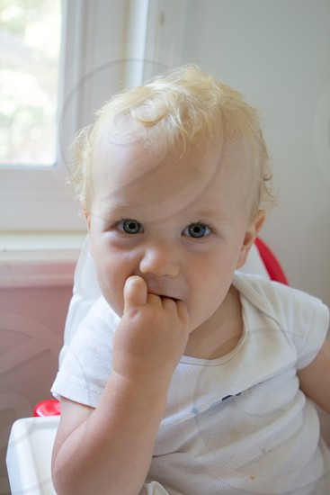 boy in white onesie biting her fingers on white highchair during daytime photo