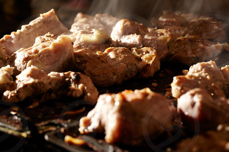 Nice pieces of meat are fried on the barbecue. Shallow dof. photo