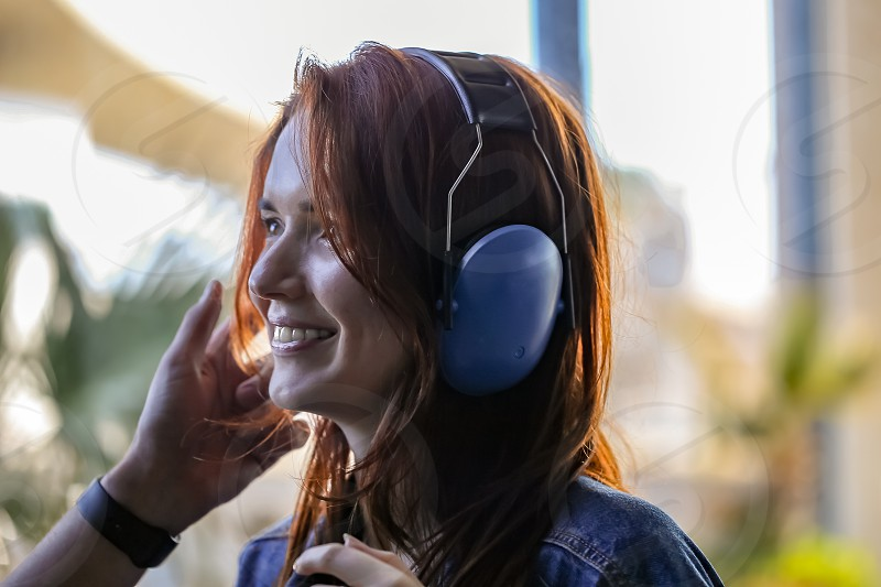 A young beautiful red-haired woman puts on antinoise headphones preparing to fly a helicopter and smiling looks forward to the journey. photo