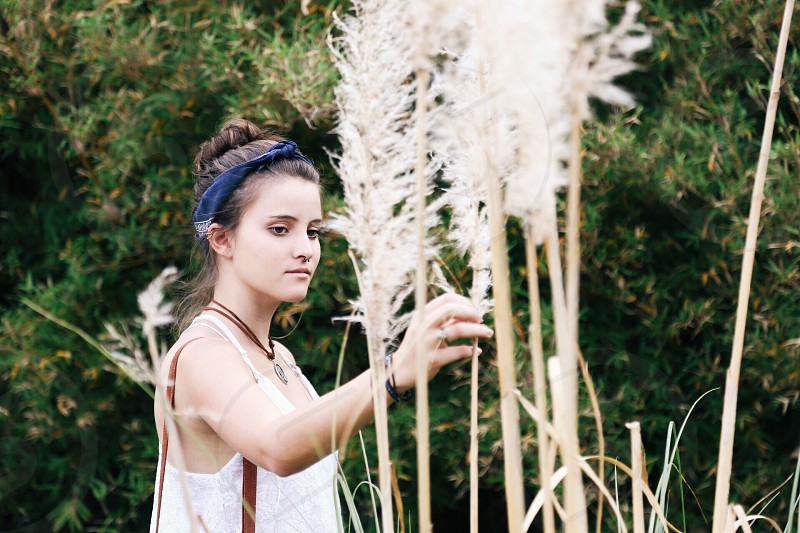 woman in white tank top looking at tall stalks of pampas grass photo