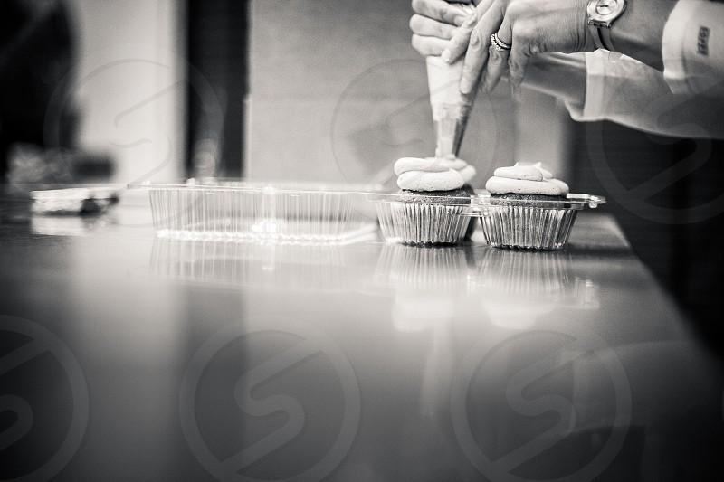 A baker decorates cupcakes. photo