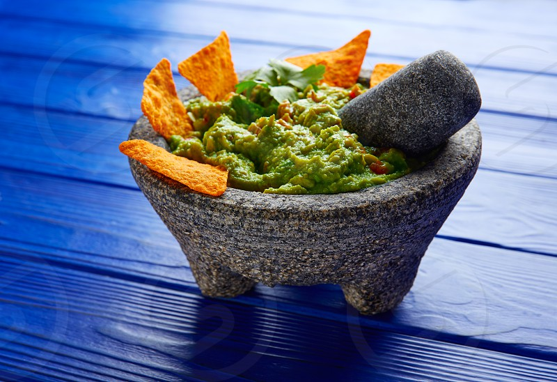 Guacamole with nachos avocado in Mexican molcajete on blue wood table photo
