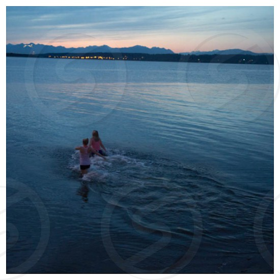 two women wading into the ocean photo