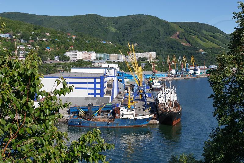 PETROPAVLOVSK-KAMCHATSKY KAMCHATKA RUSSIA - JULY 14 2013: Summer view of port Petropavlovsk-Kamchatsky and ships standing at the pier. Russia Far East Kamchatka Peninsula Avacha Bay. photo