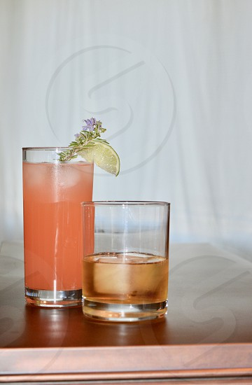 Paloma cocktail and whiskey.  Rosemary sprig and lime garnish photo