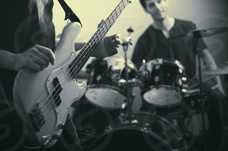 man sitting behind drum set and person holding bass guitar  photo