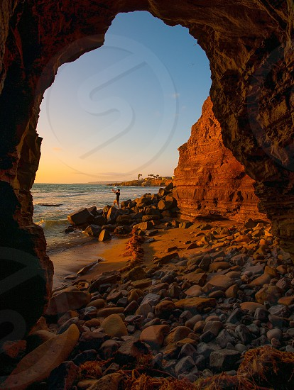 A person taking a picture of the sunset at Sunset Cliffs in San Diego photo