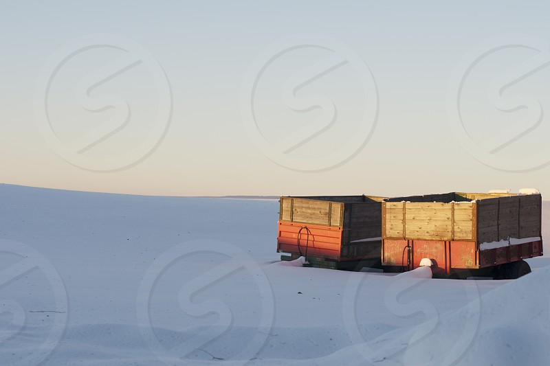 Snowy field with trailer/farm equipment. photo