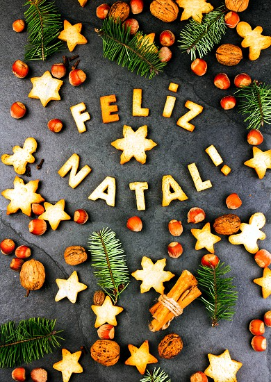 FELIZ NATAL COOKIES. Words Merry Christmas en portuguese with baked cookies Christmas decoration and nuts on black slate background. Christmas card for portuguese speaking countries top view photo
