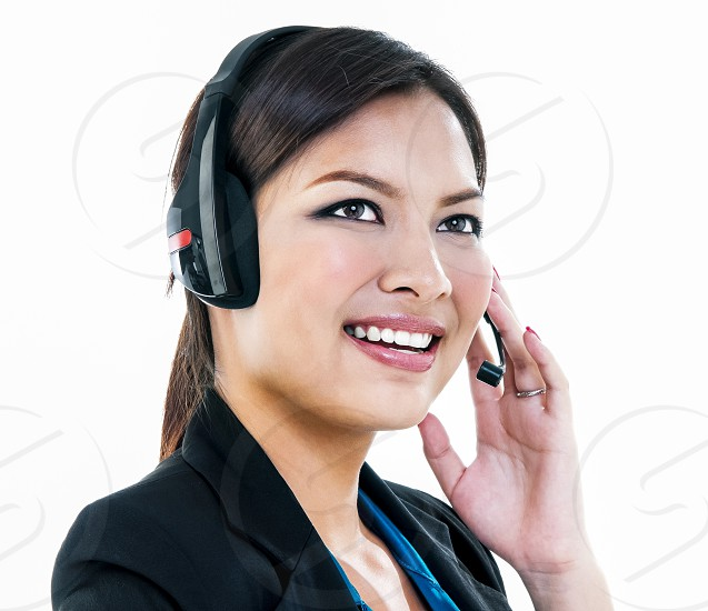 Portrait of young adult female customer service representative looking upward over white background photo