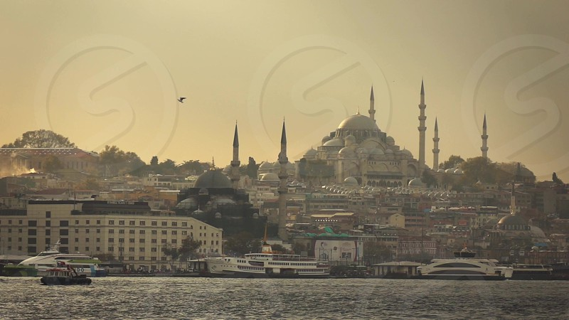 Touristic ships and boards in Golden Horn of Bosphorus strait Istanbul with looking to Suleymaniye Mosque on a sunset sky. Slow motion Full HD video 240fps 1080p. photo