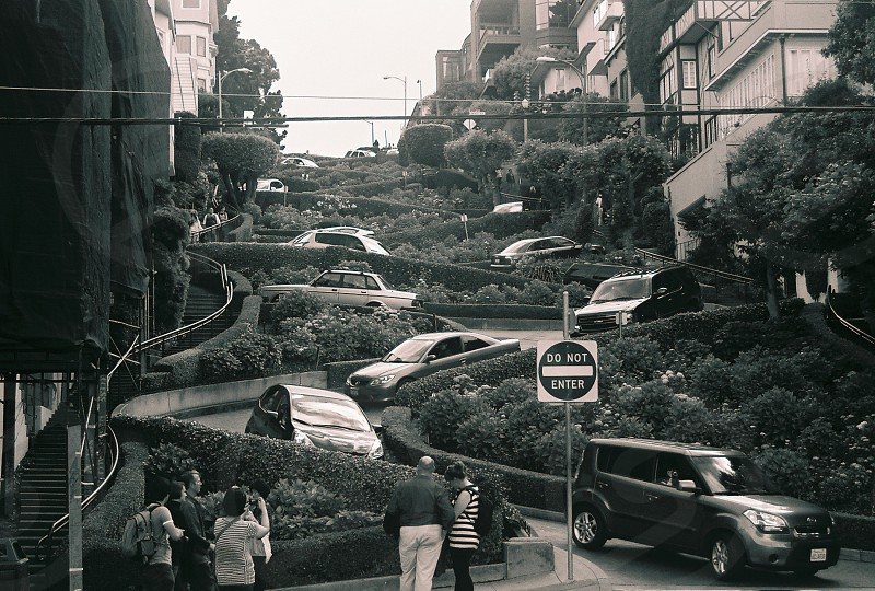 greyscale photography of people and vehicle on spiral inclined road beside trees and plants with buildings photo