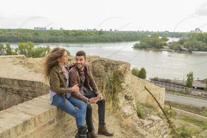 Attractive long haired woman and her boyfriend sitting on the wall and using their smartphone photo