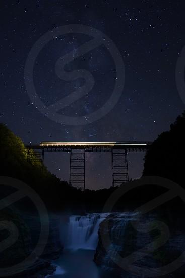 waterfalls under black metal bridge during nighttime photo