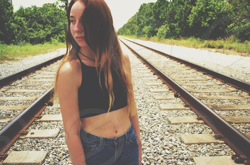 woman in black halter crop top and blue denim jeans standing on train tracks photo