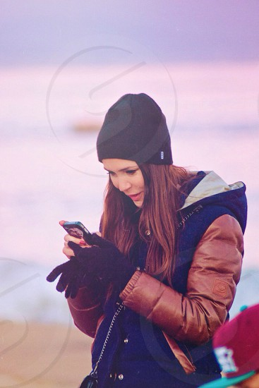woman wearing black beanie using smartphone photo