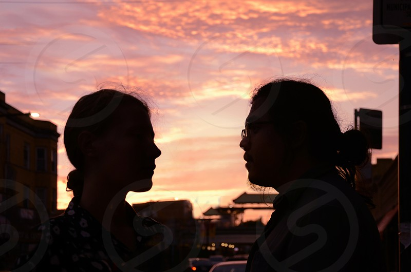 Man women silhouettes staring at each other with dramatic sunset sky and vibrant colors photo