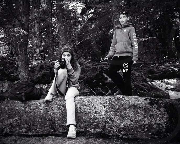 boy standing behind girl sitting on wood branch photo