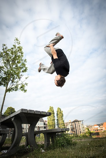 Free runner practices parkour by doing a front flip photo