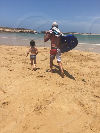photo of man in red grey and white board shorts carrying blue and black surfboard beside child in grey and black briefs standing in brown sand near body of water under blue sky during day tim photo