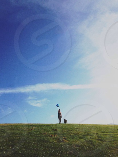 Person Standing with Dog in the Grass photo