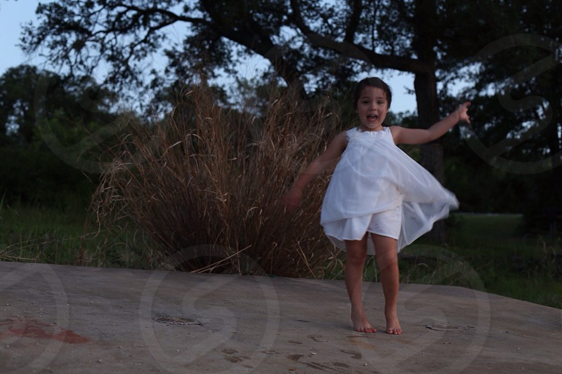 toddler wearing white dress on brown surface photo