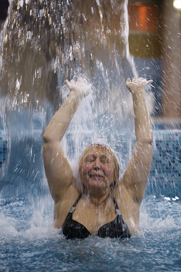 Middle-aged woman splashing in a pool under a jet of water with her arms raised and eyes closed in enjoyment photo