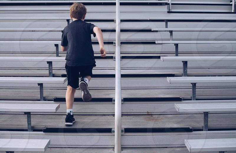 A boy running up and down bleachers.  photo