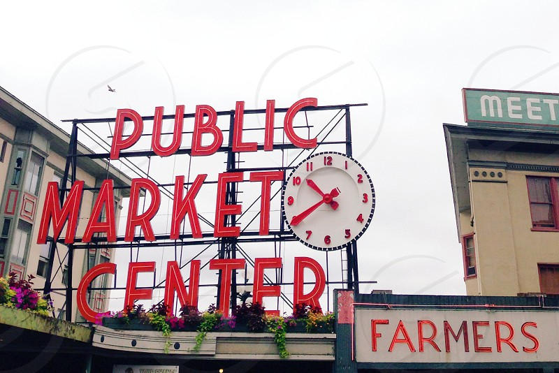 public market center with clock neon sign over a farmers market building photo