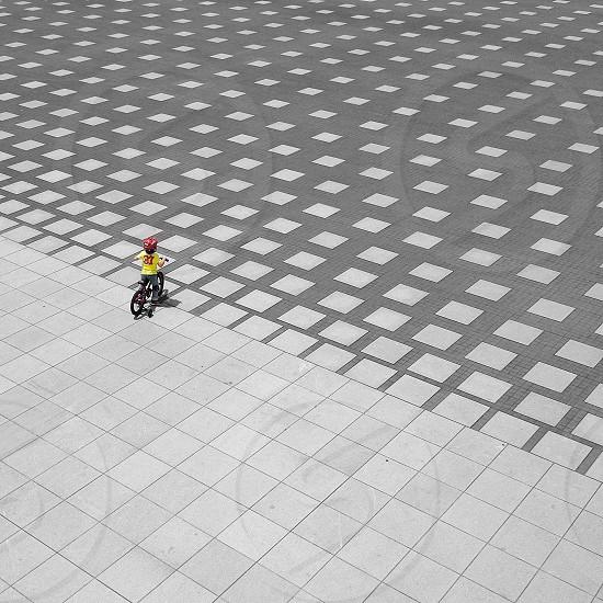 child riding a bike on a grey stone tile courtyard photo