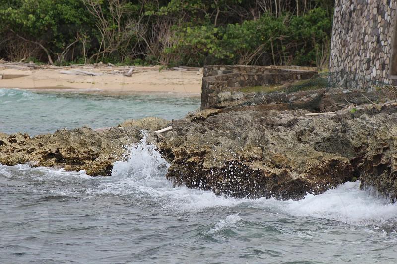 Wave crashing into a rocky shore in Jamaica photo