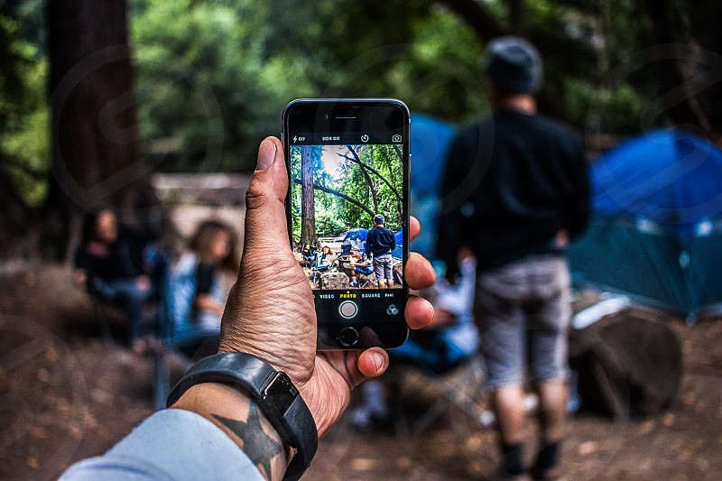 person wearing black fit bit flex  talking photo of people doing camping photo