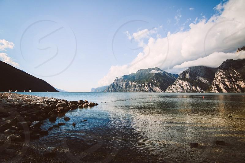 Torbole Italy lake Lake Garda sail boats clouds sky rocks mountains photo