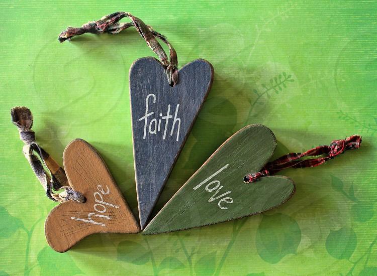 Wooden folk art hearts reading 'faith hope love' form the shape of a shamrock photo