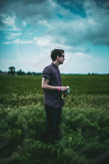 man standing on green grass and holding camera photo