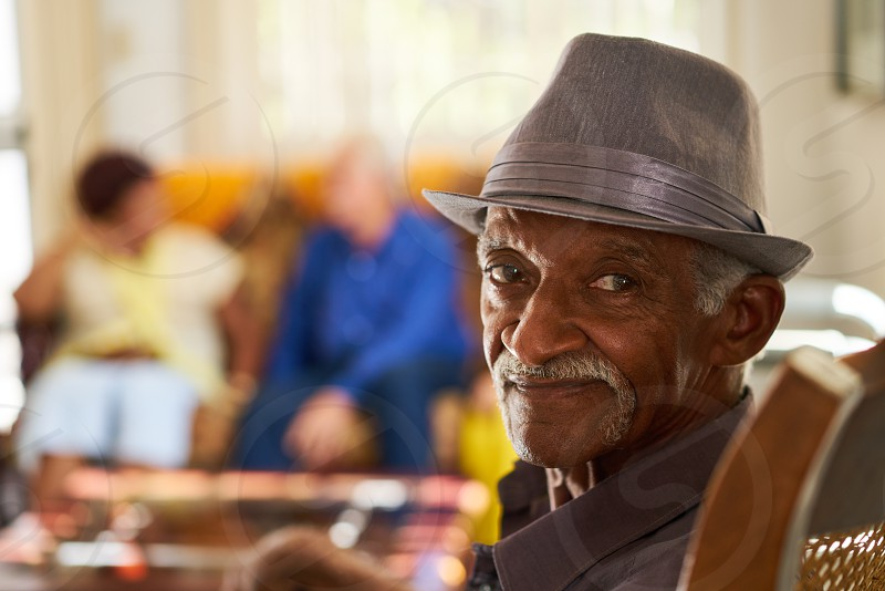Portrait of elderly black man looking at camera in retirement home with group of friends in background. Patients relaxing in hospice for seniors.  photo
