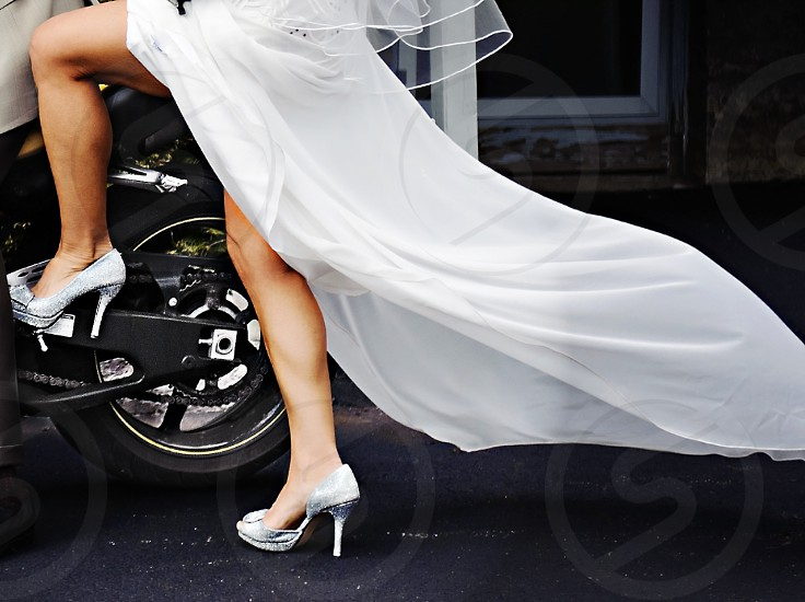 Brides legs showing as she gets on back of motorcycle as train blows in the wind. photo