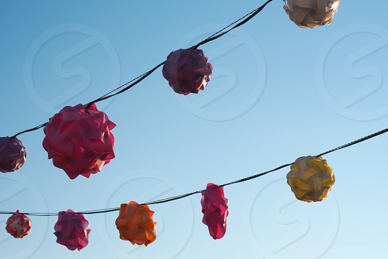 Backlit Twisted Plastic Lanterns Against Clear Blue Sky photo